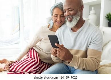 Front-View von glücklich verschiedenen Senioren Paar mit einem Smartphone auf Sofa im Strandhaus. Authentisches Konzept für das Leben im Senior