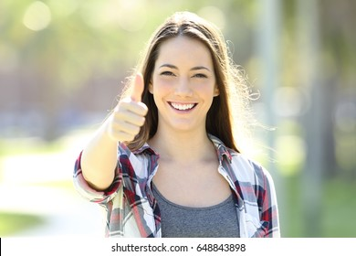Front view of a happy girl gesturing thumbs up and looking at you alone in the street