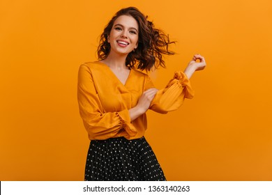 Front view of happy girl isolated on yellow background. Studio shot of blissful brunette woman in elegant blouse.