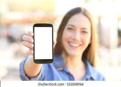 Front view of a happy girl showing a blank smart phone display and looking to the camera in the street