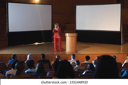 Front view of happy mixed race Businesswoman standing near podium and giving presentation to the audience in auditorium