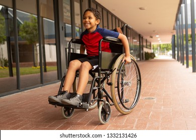 Front view of happy mixed-race disabled schoolboy sitting on wheelchair in corridor at elementary school