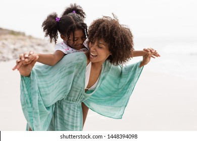 Front view of happy mixed-race mother giving piggyback ride to her cute young mixed-race daughter on the beach.