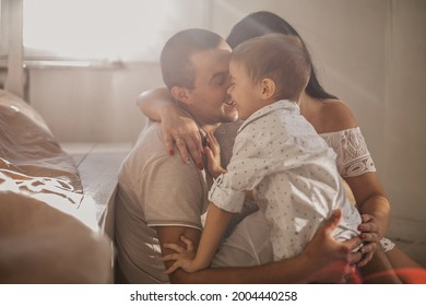 Front view of happy mother and father playing game with son at room filled with sun rays. Parents hugging child. Foster family giving wellfare to abandoned boy. Concept of mental and physical health.