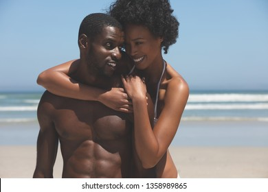 Front view of happy multi ethnic couple looking into each others eyes while standing at beach on a sunny day. They are smiling and looking in love.