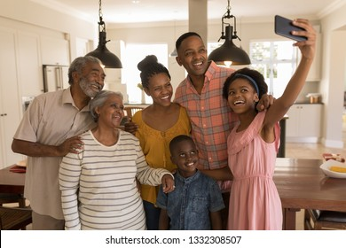 Front view of a happy multi-generation African American family taking selfie with mobile phone at home