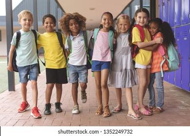 Vorderansicht der glücklichen Schulkinder, die im Korridor stehen und in den Armen zusammenhalten