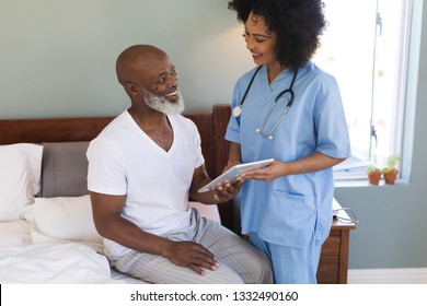 Front view of happy senior African American man and young African American female doctor using digital tablet at home