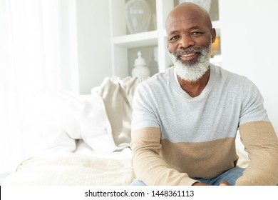 Front view of happy senior African-American man smiling while sitting on white sofa in beach house. Authentic Senior Retired Life Concept