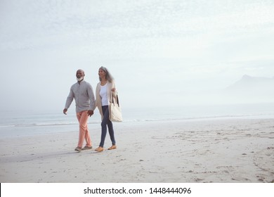 Front view of happy senior African-American couple walking hand in hand on beach on beautiful day. Authentic Senior Retired Life Concept