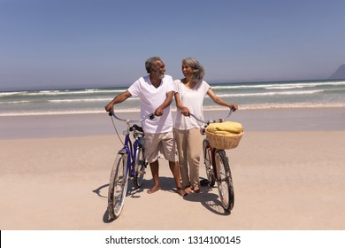 Front view of happy senior couple walking with bicycle and looking at each other on beach in the sunshine