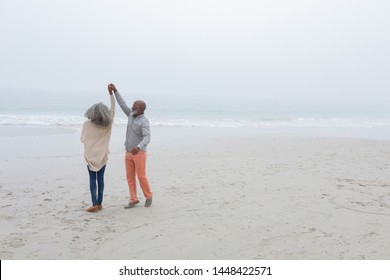 Front view of happy senior diverse couple dancing on the beach on cloudy day. Authentic Senior Retired Life Concept