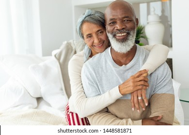 Front view of happy senior diverse couple sitting in a white room in beach house. Authentic Senior Retired Life Concept