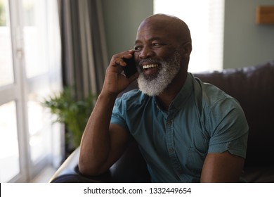 Front view of happy senior man talking on mobile phone in living room at home