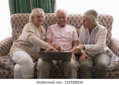 Front view of happy senior people using laptop on sofa in living room at nursing home