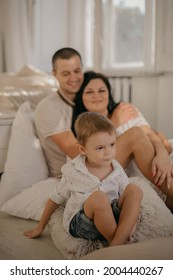 Front view of happy smiled boy with mother and father on background. Smiled  parents hugging and small son playing, sitting on couch. Adopted child with lovely family. Concept of healthy relationship.