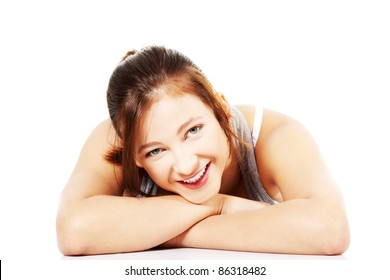 Front view of happy smiling teen girl lying on her tummy on white background