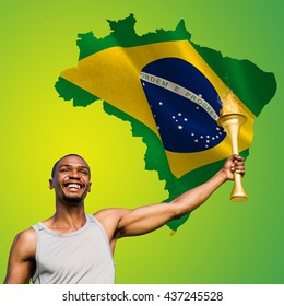 Front view of happy sportsman holding a cup against green brazil outline with flag