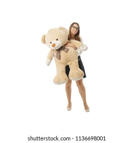 front view of happy woman playing with huge teddy bear on white background