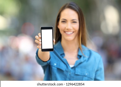 Front view of a happy woman showing smart phone screen mock up in the street