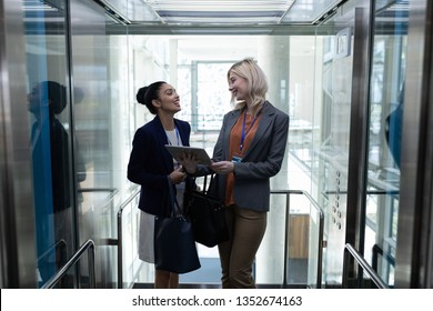 Front view of happy young multi-ethnic businesswomen discussing over digital tablet in modern office elevator. They are smiling