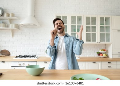 Front view head shot overjoyed young man using kitchenware as microphone, singing favorite song. Happy carefree guy having fun alone at modern kitchen, preparing breakfast at weekend morning.