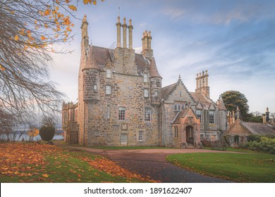 Front view of the historic tourist attraction 16th century Lauriston Castle in autumn with sunrise or sunset golden light in Edinburgh.