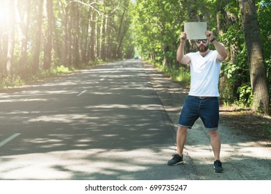 Front view. Hitchhiking. Guy is traveling.Young bearded hipster man, dressed in denim shorts and white T-shirt,stands on side of empty road, holds sign in his hands and stops passing cars. Film effect