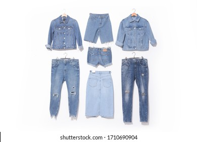 Front view hole and threads of two blue jeans  and two jeans jacket on hanging with back view shorts jeans jeans skirt on white background