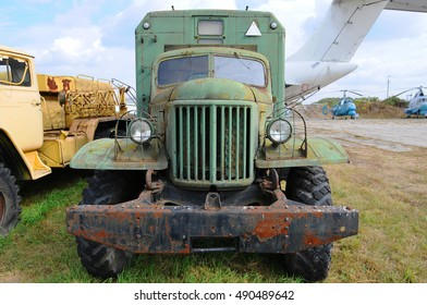 Front view of hood grill and bumper of rusted green truck in field and other technique