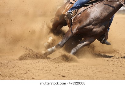 A front view of a horse galloping and sliding in the dirt.