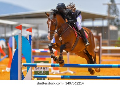 Front view of horse rider jumping over the obstacles during the horse jumping competition