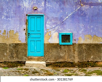 A front view of a house with old, violet wall with peeling paint and turquoise blue door and tiny window