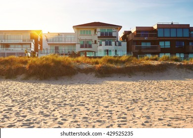 Front view of house on the beach and a setting sun, real estate with space for text