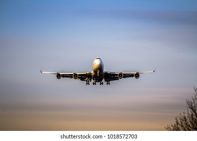 Front view of a jet airplane approaching an airport for landing