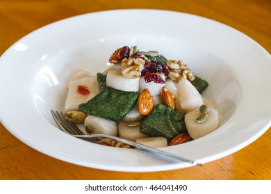 Front View of Korean Cooked Rice Cakes in White Bowl with Fork Topped with Almonds, Dried Cranberries, Walnuts, and Pumpkin Seeds on Wood Table