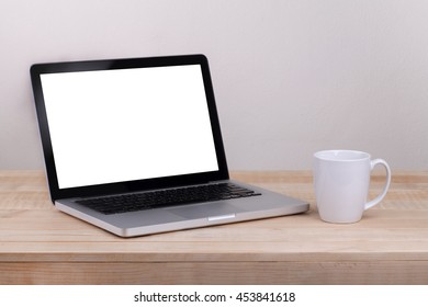 Front view of the laptop and coffee is on the work table concrete background