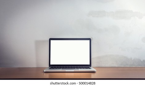 Front view of the laptop is on the work table, concrete background, clipping path inside