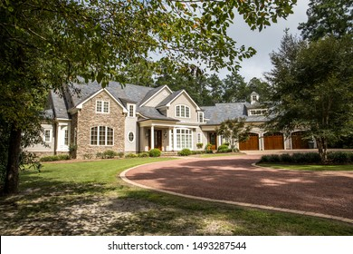 Front view of large estate home in the south with a gravel driveway and lots of windows. house made of brick, stone and clapboard in a cape cod style. and a triple garage with curb appeal