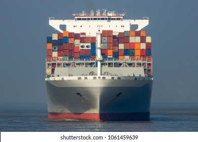 Front view of a large shipping container ship in the ocean.