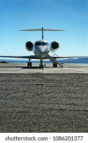 Front View of a Lear jet on a tarmac ready to fly with passengers.