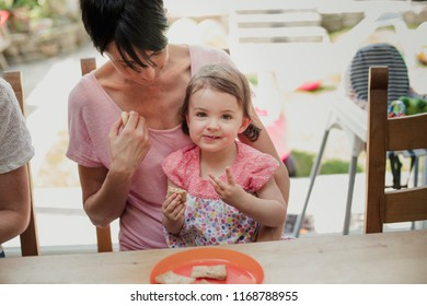 Front view of a little girl looking at the camer and enjoying a little sandwich. The little girl is sitting on her mothers lap.