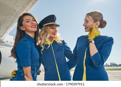 Front view of a lovely young stewardess in uniform standing next to her female colleagues