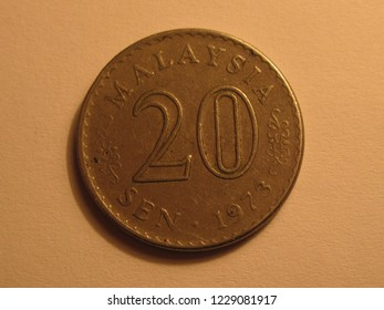Front view of Malaysian coin. 20 sen from Malaysia. Great for numismatic collection. Shiny copper coin isolated on yellow surface of paper.