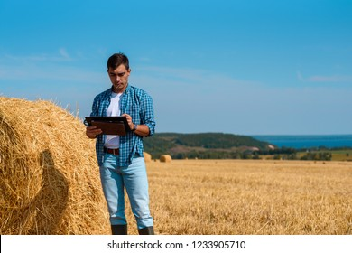 Front view of male agronomist farmer with a tablet in blue jeans and shirt and white t-shirt in field with haystacks