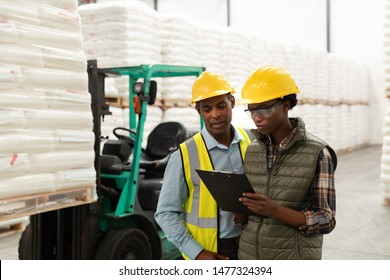 Front view of male and female worker discussing over clipboard in warehouse. This is a freight transportation and distribution warehouse. Industrial and industrial workers concept