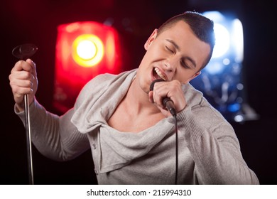 front view of male singer holding stand. handsome man singing into microphone alone