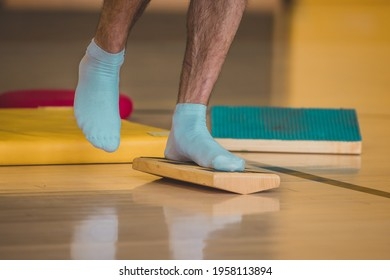 Front view of male trainer seen using a wooden balance board. Different balance sports equipment is seen around in a gym indoors.