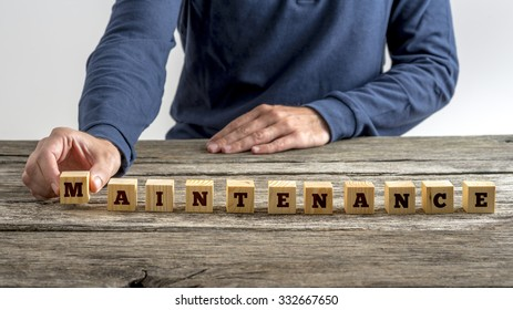 Front view of a man assembling the word Maintenance with wooden cubes.