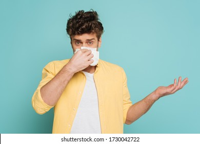 Front view of man blowing out nose with napkin, pointing with hand and looking at camera isolated on blue